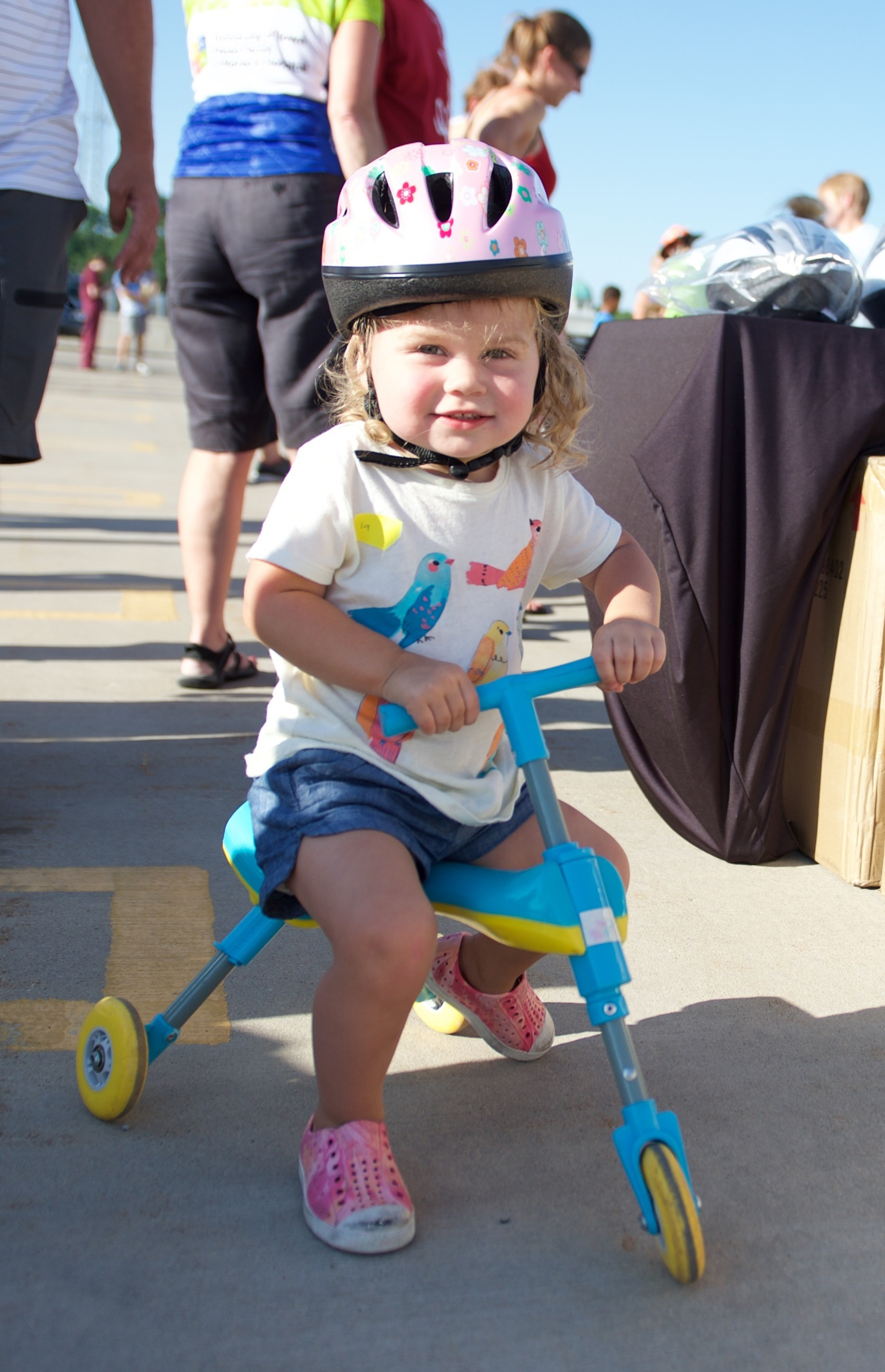 child on tricycle wearing a helmet
