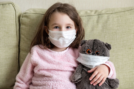 Child wearing mask with her teddy bear