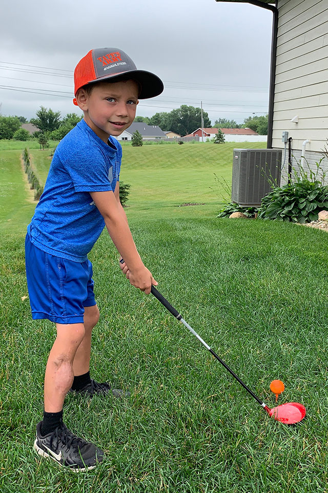 Tate Manahl playing golf in back yard